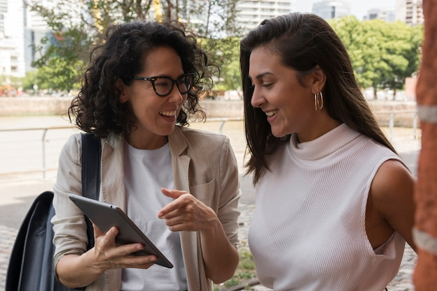 Beautiful business women looking at a tablet outside Free Photo