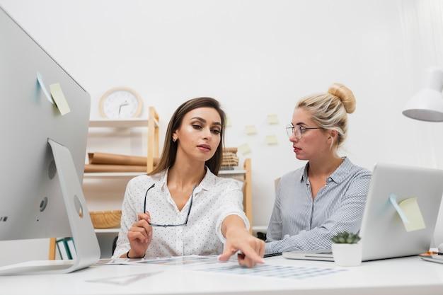 Beautiful business women sitting on office Free Photo