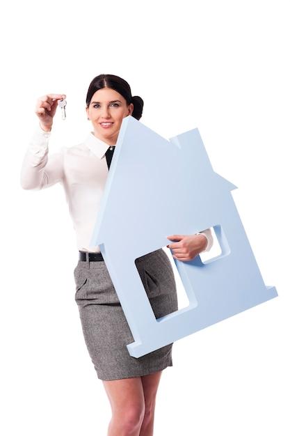 Красивая деловая женщина держит знак дома и ключи для него Бесплатные Фотографии
