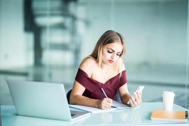 Красивая деловая женщина, работающая, сидя за своим столом в офисе Бесплатные Фотографии