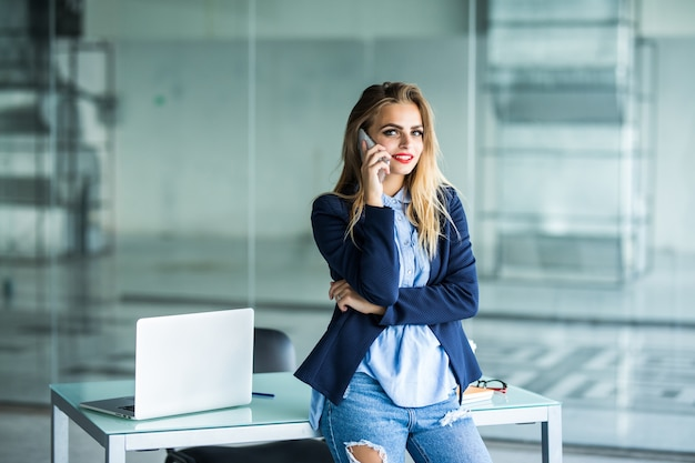 Beautiful busy businesswoman, standing in office, writing in planner and talking on mobile phone. Free Photo