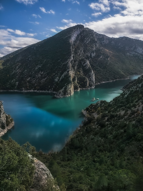 Beautiful & calm emerald river, before a mountain & a forest nearby in catalunya, spain Premium Photo