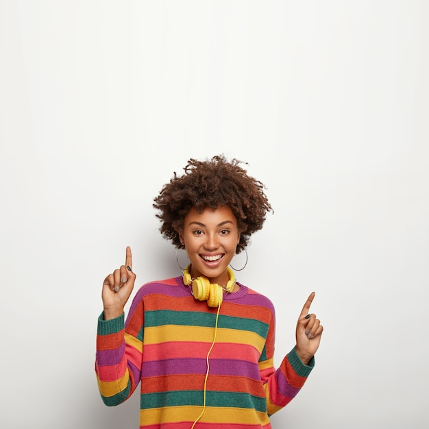 Beautiful carefree hipster girl with afro hairstyle, moves against white wall, points upwards, says your text here, uses yellow headphones for listening favourite music, wears striped colored jumper Free Photo