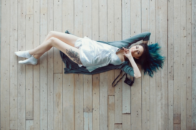 Beautiful carefree young casual woman lying on the wooden floor Free Photo