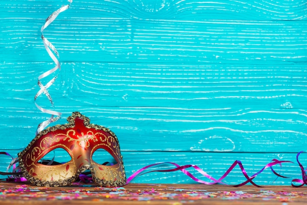 Beautiful carnival mask on blue wooden background Free Photo