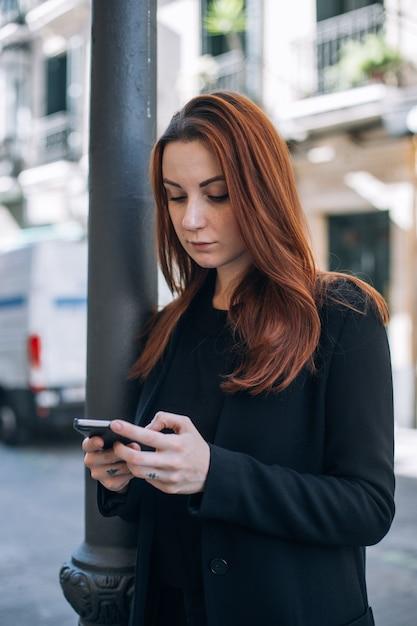 赤い髪とナチュラルメイクの美しいカジュアルな女性が通りに立って、スマートフォンでテキストやチャットをします 無料写真