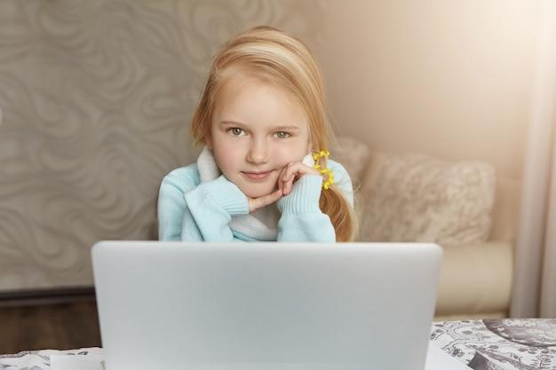 開いているラップトップコンピューターの前に座っている美しい白人金髪少女 無料写真
