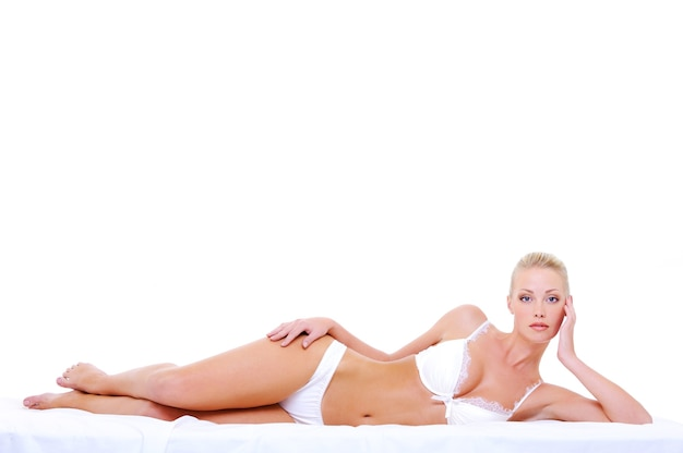 Beautiful caucasian blonde woman with perfect sexy body lying down on the bed Free Photo