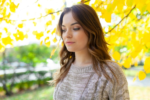 Beautiful caucasian brunette girl standing warm autumn day with background of trees with yellow foliage Premium Photo