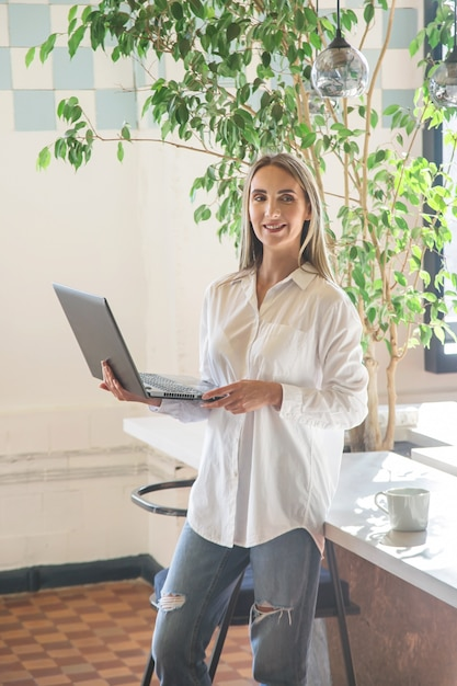 Beautiful caucasian girl holding a laptop in her hands in the office. Premium Photo