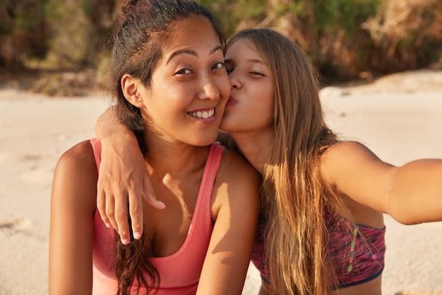 美しい白人の女の子は彼女のガールフレンドの頬にキスします 無料写真