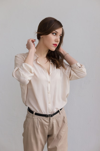 Beautiful caucasian girl with red lips in stylish beige blouse looks thoughtfully aside. loneliness concept Premium Photo