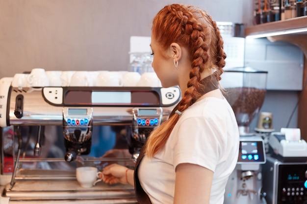 Bella signora caucasica sorridente che prepara caffè caldo presso la moderna caffetteria Foto Gratuite