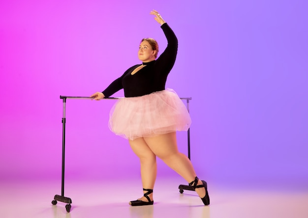 Красивая кавказская модель большого размера, практикующая балет на градиентном фиолетово-розовом фоне студии в неоновом свете. понятие мотивации, включения, мечты и достижения. стоит быть балериной. Бесплатные Фотографии