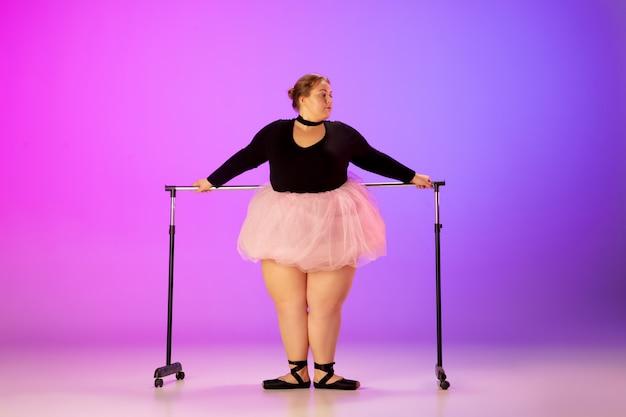 네온 불빛에 그라데이션 퍼플 핑크 스튜디오 배경에 발레 댄스를 연습하는 아름다운 백인 플러스 사이즈 모델. 동기 부여, 포용, 꿈 및 업적의 개념. 발레리나가 될만한 가치가 있습니다. 무료 사진