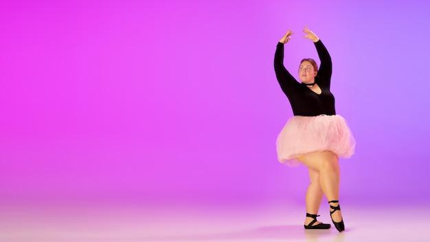 ネオンの光の中でグラデーション紫ピンクのスタジオの背景にバレエダンスを練習する美しい白人プラスサイズのモデル。モチベーション、インクルージョン、夢と成果の概念。バレリーナになる価値があります。 無料写真