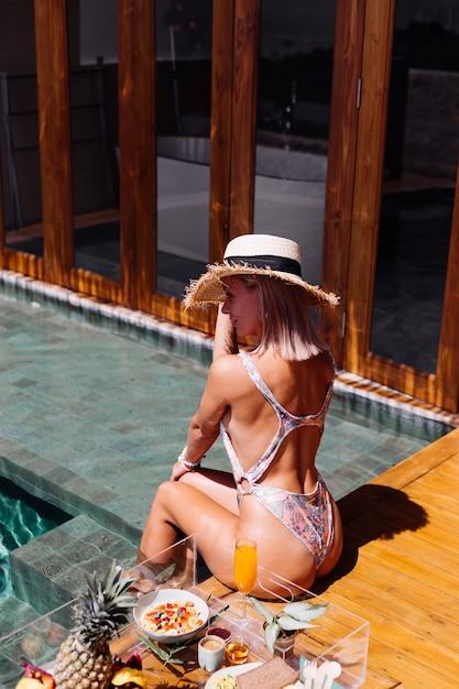 Красивая кавказская загорелая женщина в бикини и соломенной шляпе с плавающим завтраком на удивительной роскошной вилле в стиле бали в солнечный день у бассейна, на тропическом фоне. Бесплатные Фотографии