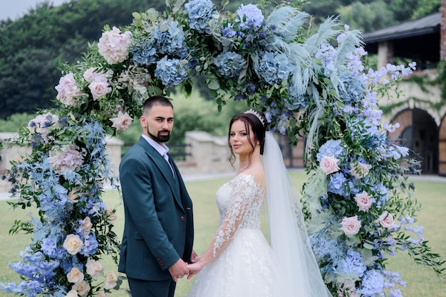 Beautiful caucasian wedding couple is standing in front of decorated with blue hydrangea archway and holding hands together Free Photo