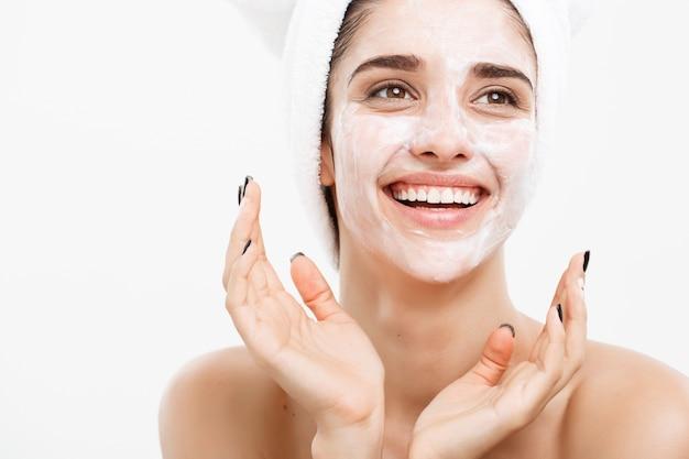 Beautiful caucasian woman face portrait applying cream mask on her ...