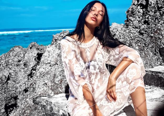 Красивая модель кавказской женщины с темными длинными волосами в прозрачной белой длинной блузке платье позирует возле скал и голубого неба и океана Бесплатные Фотографии