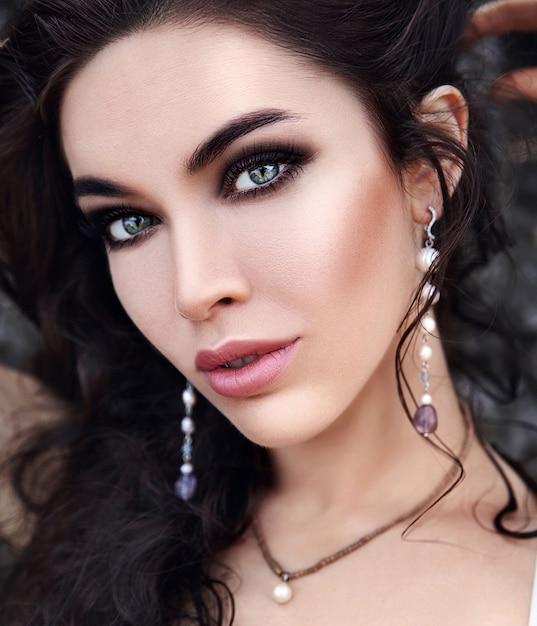 Beautiful caucasian woman with evening makeup and dark long hair outdoors Free Photo
