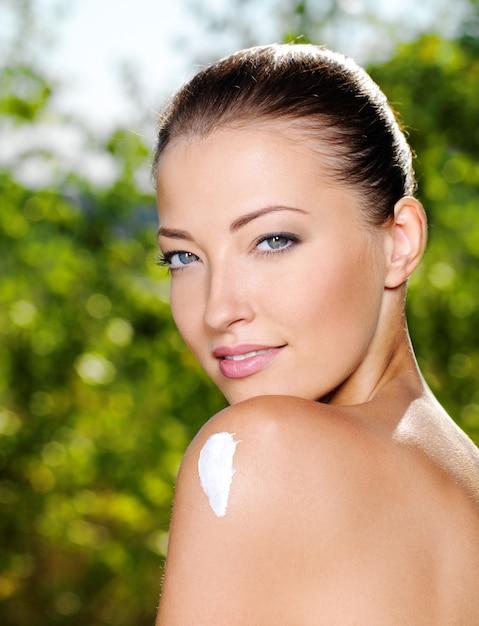 肩に保湿剤ceamを持つ美しい白人女性 無料写真