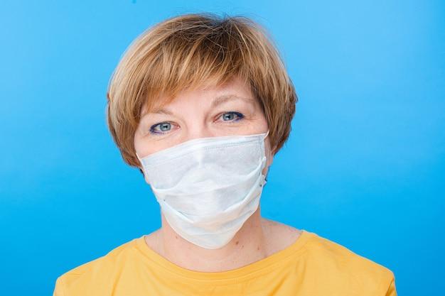 特別な医療マスクを持つ美しい白人女性は幸せです、青い背景で隔離の肖像画 無料写真