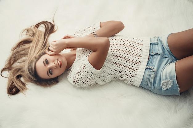 Beautiful charming blonde long hair lying on bed Premium Photo