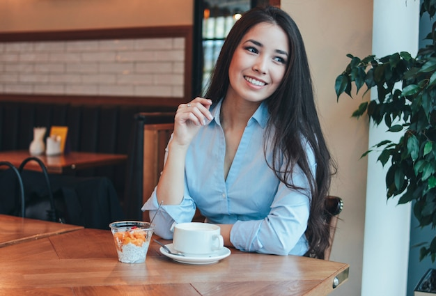 Beautiful charming brunette smiling asian girl has breakfast with coffee and chia pudding at cafe Premium Photo