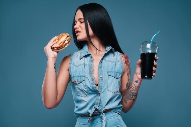 Beautiful charming tattoo girl with hamburger and soda Premium Photo