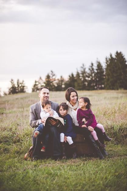 Красивая веселая семья с мамой, отцом и тремя детьми, читающими библию в парке Бесплатные Фотографии