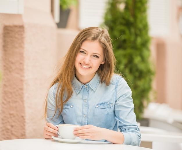 Beautiful cheerful woman sitting in summer cafe. Premium Photo
