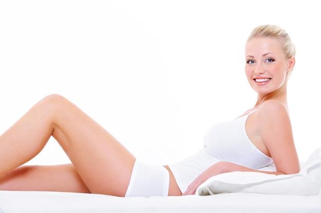 ベッドに横になって白いランジェリーで完璧な美脚を持つ陽気な美人 無料写真