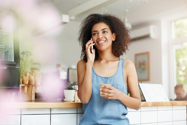 Говорить красивого жизнерадостного молодого африканского студента женщины усмехаясь на телефоне выпивая кофе в кафе. Бесплатные Фотографии