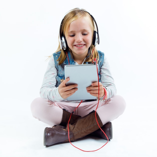 Beautiful child listening to music with digital tablet. Free Photo