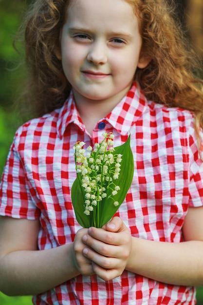 Красивый ребенок с лесом ландыша весной. Premium Фотографии