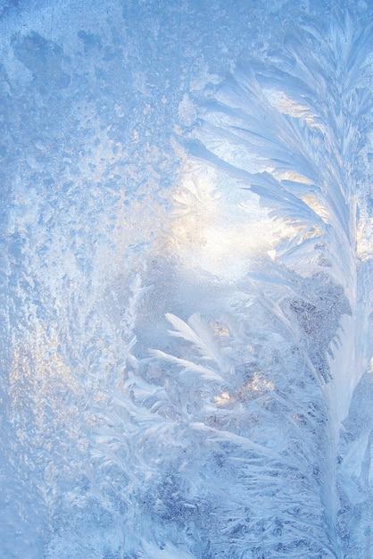 Красивый новогодний фон с синим морозным узором на стекле Premium Фотографии