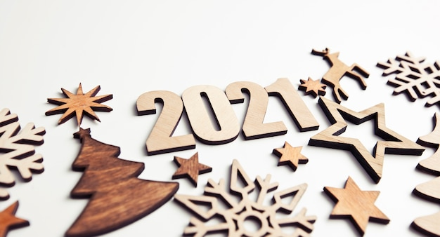 The beautiful christmas background with a lot of small wooden decorations and wooden numbers 2021 on the white desk. Premium Photo