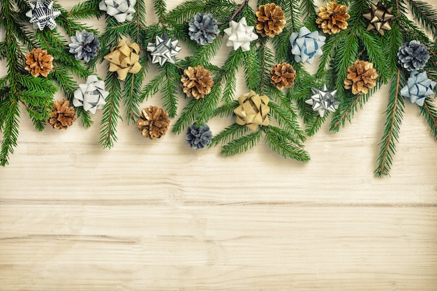 Beautiful christmas composition of fir branches decorated with bows and cones Premium Photo