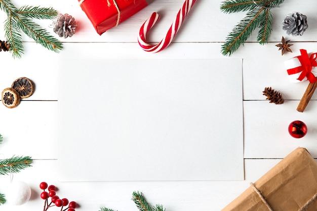木製の白い背景の上の美しいクリスマスの構成。クリスマスプレゼントボックス付きの空のカード Premium写真