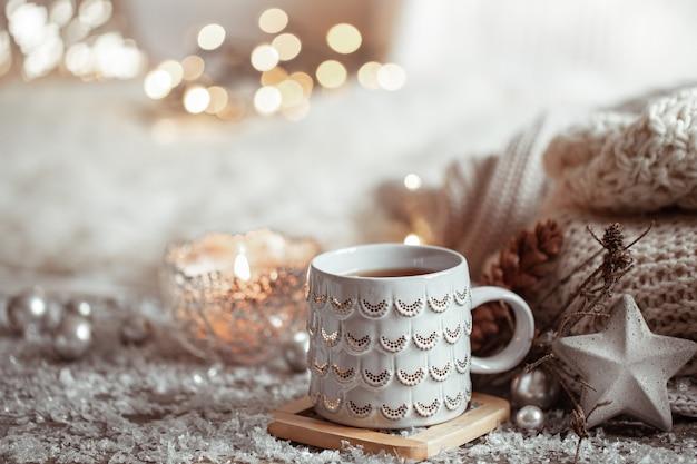 Красивая рождественская чашка с горячим напитком на светлой размытой стене. понятие домашнего уюта и тепла. Бесплатные Фотографии