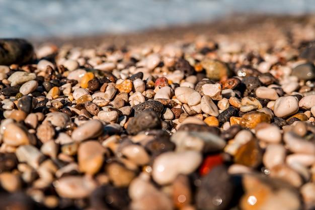 Красивое чистое море. волна плыла по цветной морской гальке на берегу. Premium Фотографии