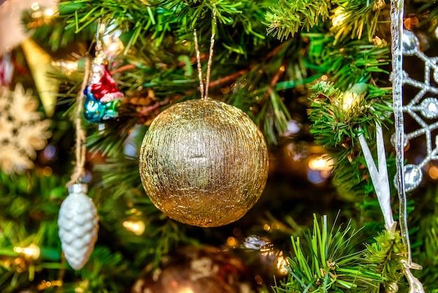 황금 공 및 조명과 함께 크리스마스 트리에 다른 장식의 아름다운 근접 촬영 무료 사진