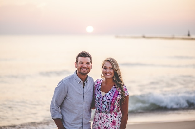 Beautiful closeup portrait of a young couple posing in front of a stunning seascape Free Photo