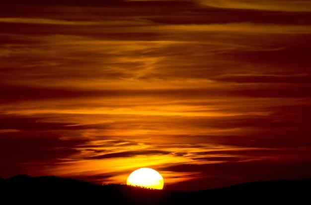 イタリア、トスカーナの空と半分の太陽を読んだ夕日の美しいクローズアップショット 無料写真