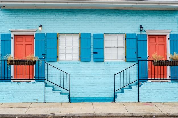 Bella combinazione di colori delle scale che conducono ad appartamenti con porte e finestre simili Foto Gratuite