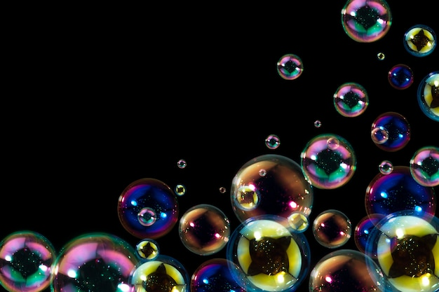 Beautiful of colorful soap bubbles float on black background. Premium Photo
