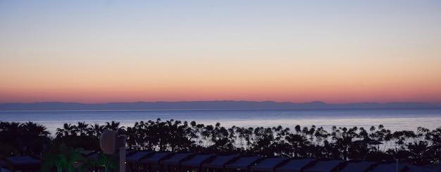 海と太陽に沈む美しいカラフルな夕日。オレンジ色の空。 無料写真