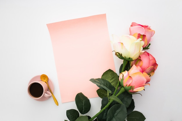 Beautiful composition with coffee, pink roses and blank paper on white Free Photo