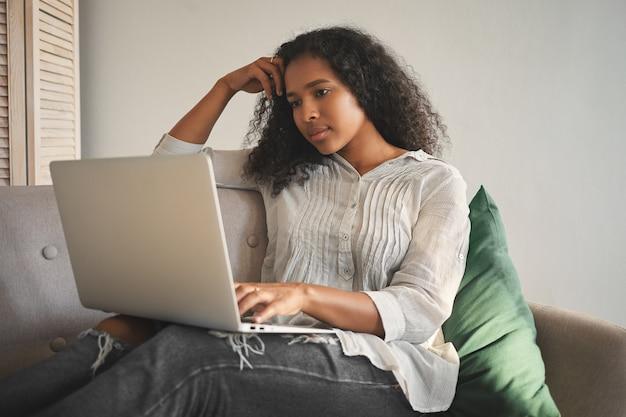 Bella giovane femmina dalla pelle scura concentrata con acconciatura afro che studia a distanza tramite corsi online, utilizzando il wifi sul suo laptop mentre è seduto sul divano di casa. persone, tecnologia e istruzione Foto Gratuite